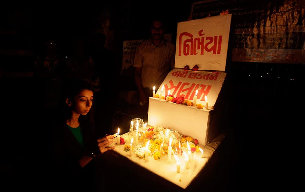 A young Indian girl places a candle in rememberance of last year's gang rape and murder of a young woman in New Delhi, in Ahmadabad.