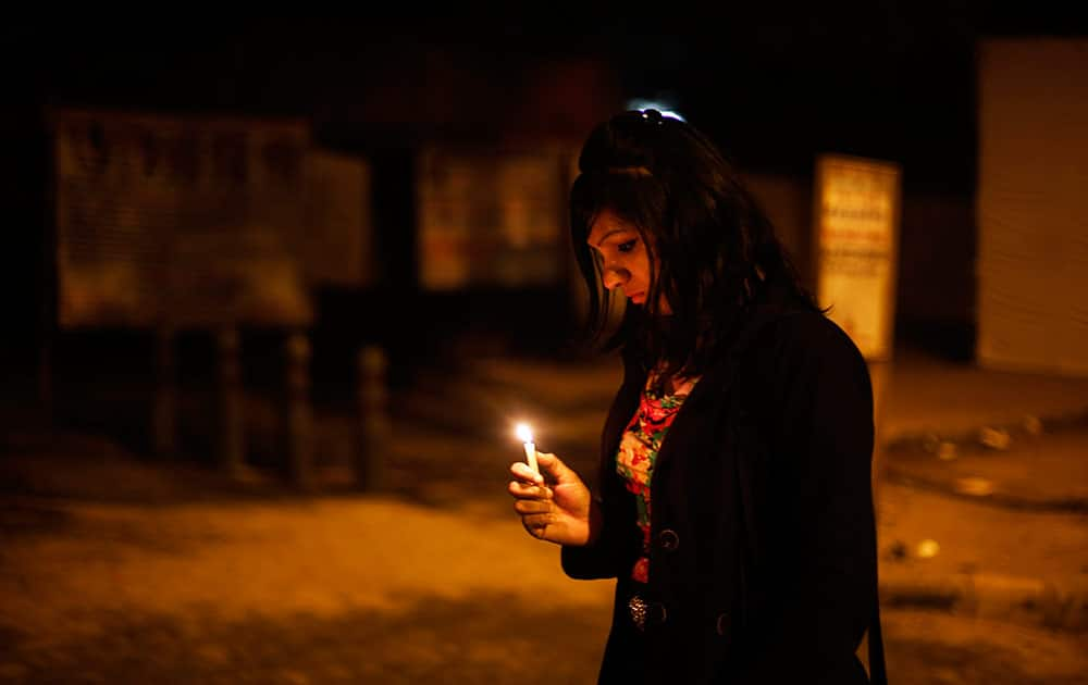 A young Indian woman holds a candle as she joins others in commemorating last year's gang rape and murder of a young woman in New Delhi.