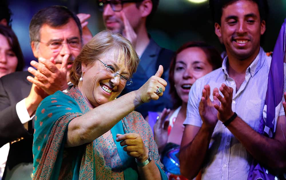 Presidential candidate and former President Michelle Bachelet gives the thumbs up sign during a victory rally in Santiago, Chile.