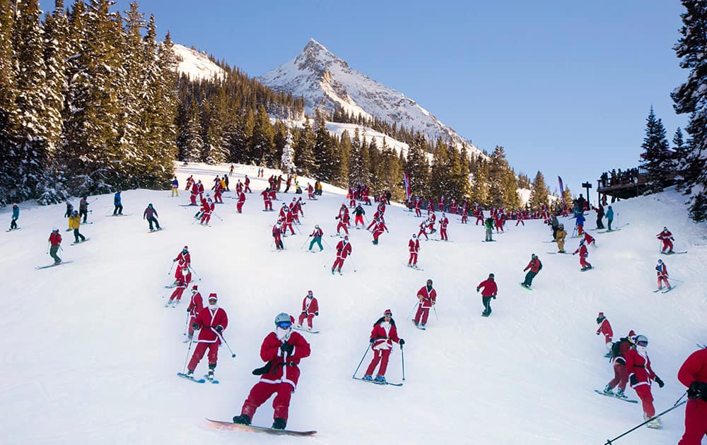 In this hand out image provided by Crested Butte Mountain Resort, shows participants dressed as Santas skiing from Uley`s Ice Bar on Crested Butte Mountain, Crested Butte, Colo., for the first `Santa Ski Crawl`.