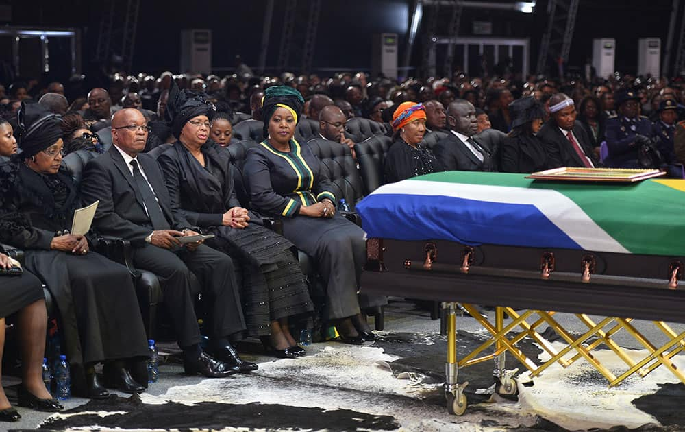 South African President Jacob Zuma sits between Winnie Madikizela-Mandela, left, Nelson Mandela`s former wife, and Nelson Mandela's widow Graca Machel during the funeral service for former South African President Nelson Mandela in Qunu, South Africa.