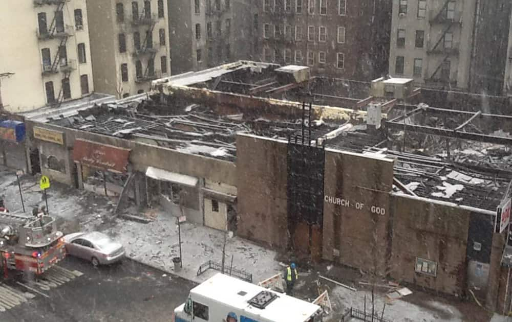 In this image taken from video, New York City firefighters and emergency workers look over the scene on Saturday, Dec. 14, 2013, after a 4-alarm fire engulfed multiple buildings Friday night, in the Harlem neighborhood of New York. Officials say more than 100 firefighters responded.