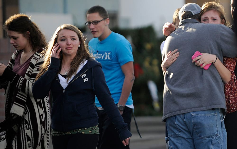 Chris Foster hugs his daughter Devan, after they reunited at the Kings Sooper parking lot of Arapahoe High School after a shooting on the campus in Centennial, Colo.