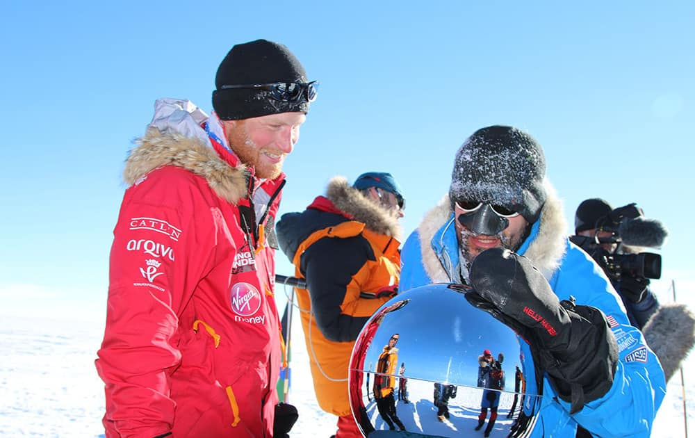 Britain`s Prince Harry and Ivan, touch the pole, as they and their fellow adventurers reach the South Pole, as part of their Walking With The Wounded charity trek.