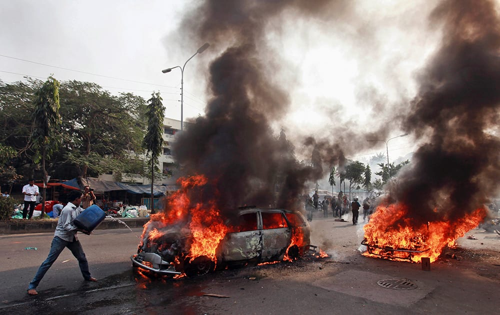 A Bangladeshi man tries to extinguish a car set afire by Islamist party Jamaat-e-Islami activists following the execution of their party leader Abdul Quader Mollah in Dhaka, Bangladesh.