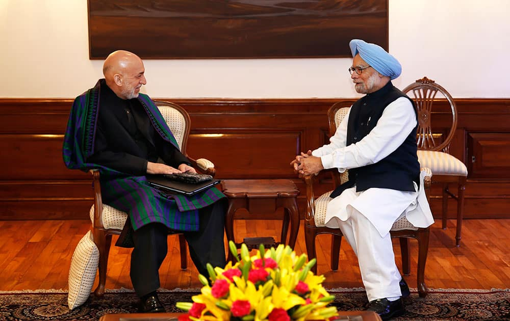Indian Prime Minister Manmohan Singh, right, talks to Afghanistan President Hamid Karzai at his residence in New Delhi.