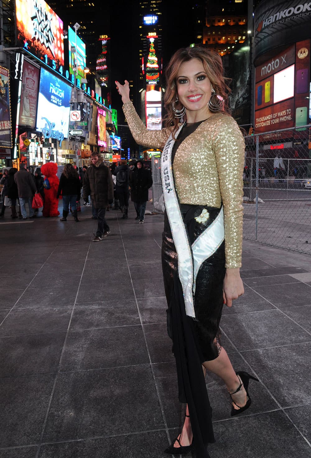 Erin Brady, Miss USA 2013, points to the 150-foot tall digital Christmas tree atop One Times Square on the Toshiba Vision and TDK screens, in New York.