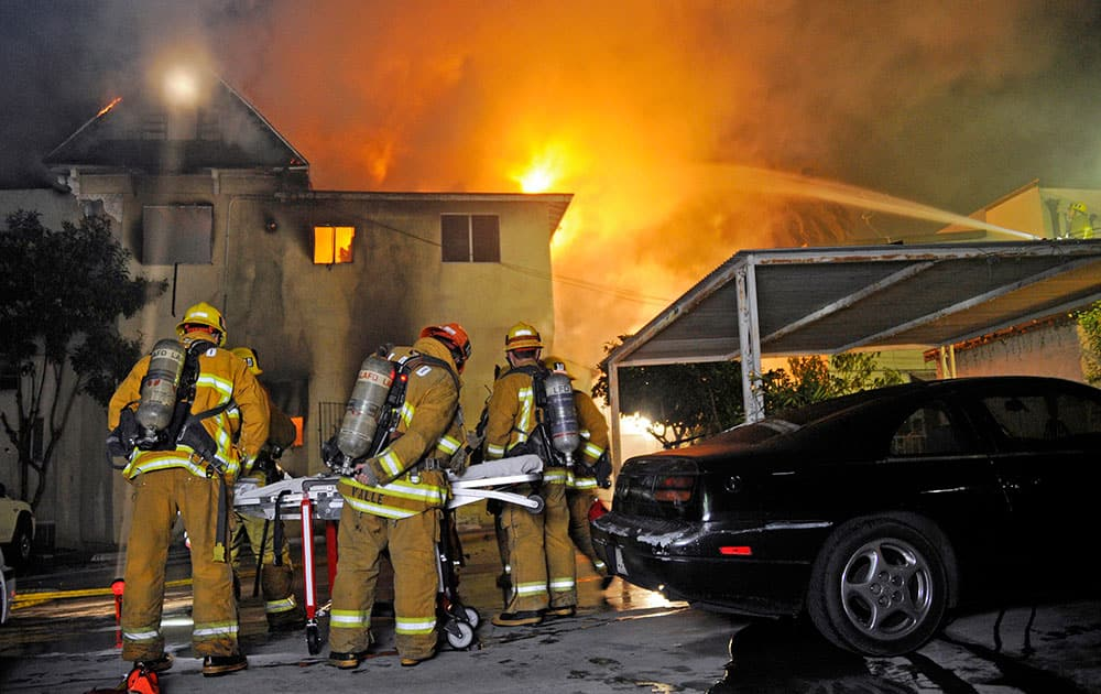 Los Angeles firefighters battle a predawn fire that tore through an apartment building in the Echo Park district, killing two people and injuring three others.