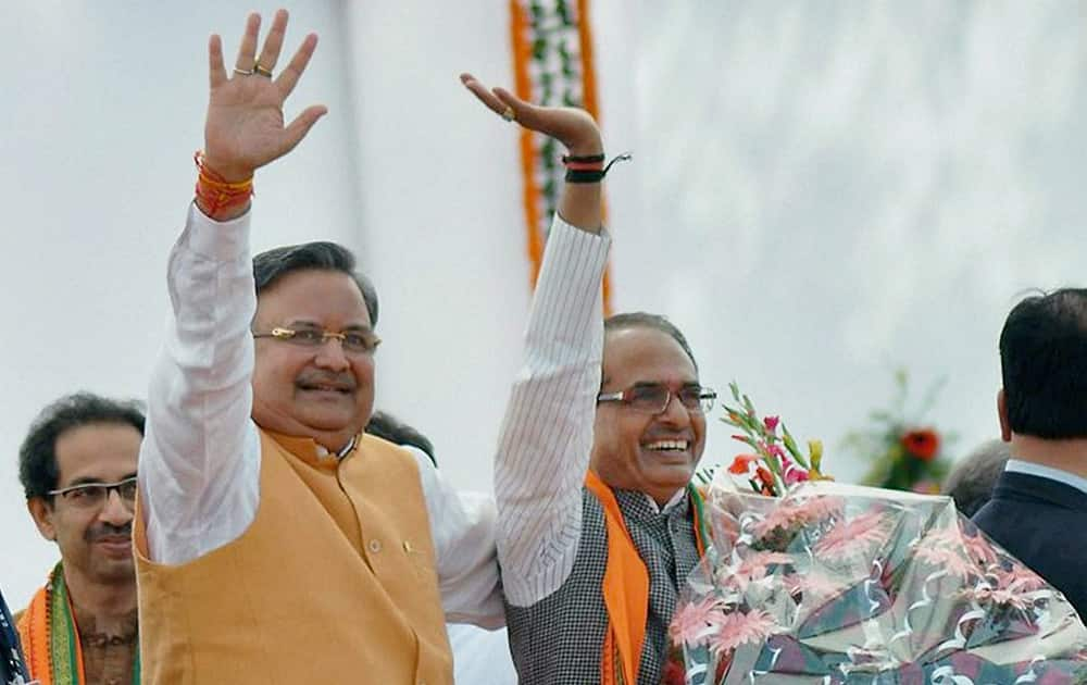 Chhattisgarh CM Raman Singh along with Madhya Pradesh CM Shivraj Singh Chouhan waves at the crowd during his swearing-in ceremony, in Raipur.