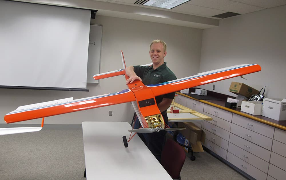 University of North Dakota aviation student Logan Lass lifts a lightweight drone used in training at the Grand Forks, N.D. school`s unmanned aircraft program.