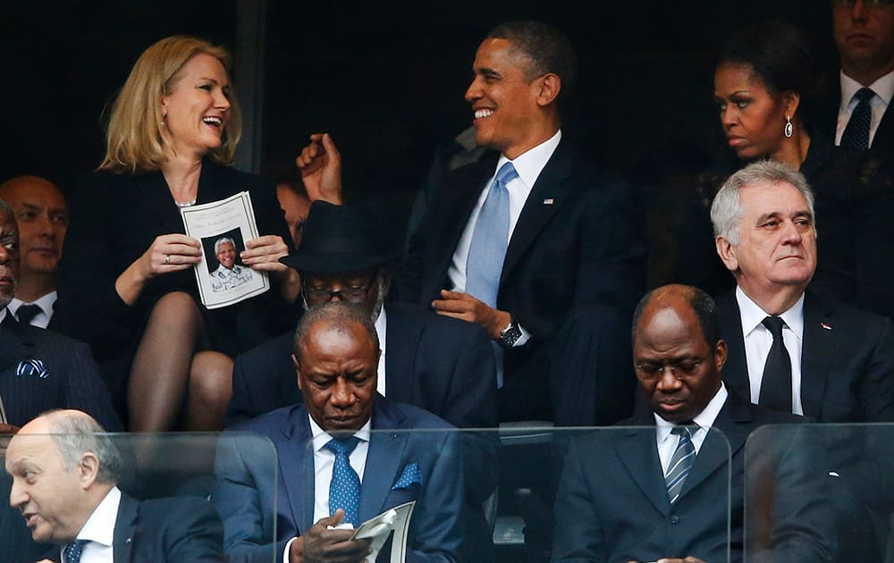 President Barack Obama jokes with Danish prime minister, Helle Thorning-Schmidt as first lady Michelle Obama looks on at right during the memorial service for former South African president Nelson Mandela at the FNB Stadium in Soweto, near Johannesburg, South Africa.