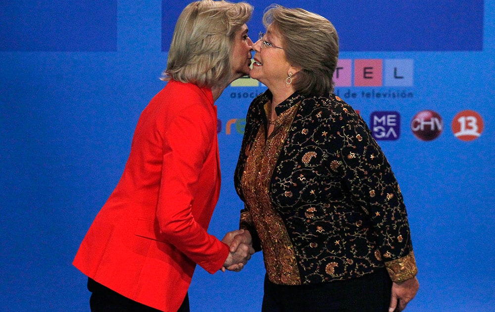 Chile`s presidential candidates, Michelle Bachelet, right, and Evelyn Matthei greet, obliging photographers` requests for a kiss before their television debate in Santiago, Chile.