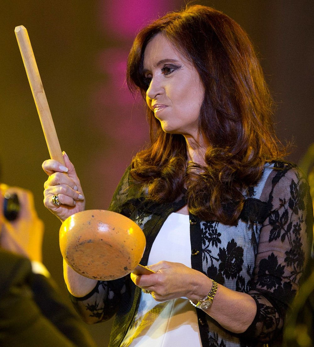 Argentina`s President Cristina Fernandez bangs a pot during an event to celebrate the 30 year anniversary of the return of democracy outside the Government Palace, known as `Casa Rosada`, in Buenos Aires, Argentina.