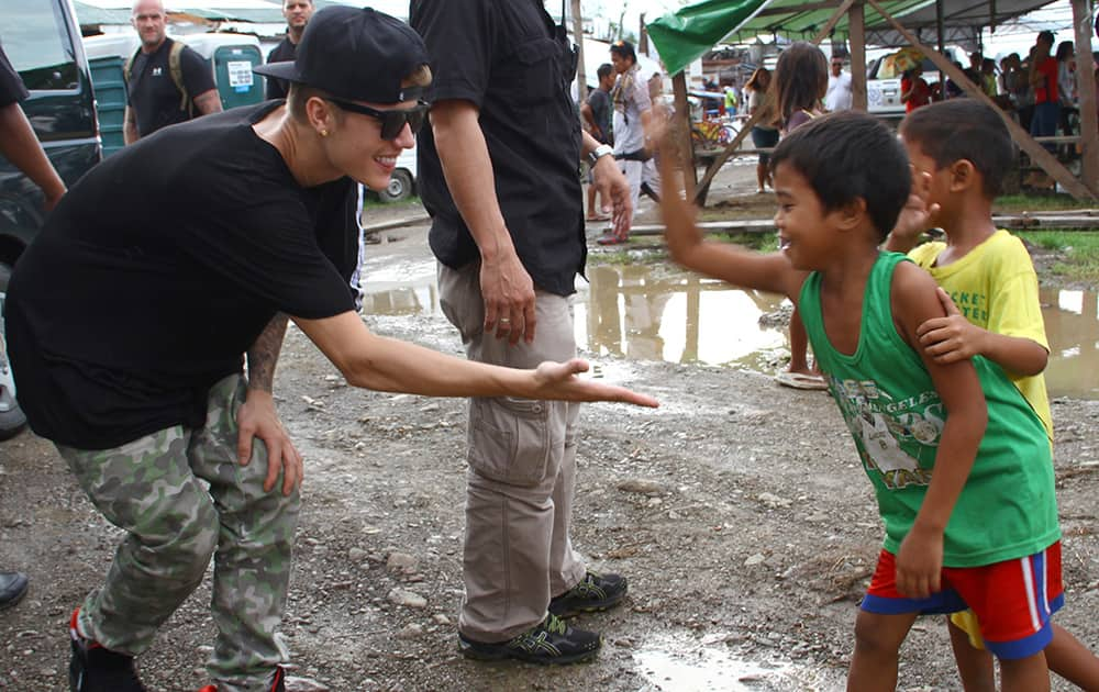 Justin Bieber exchanges high-fives with children survivors of typhoon Haiyan during his visit to Tacloban city, Leyte province in central Philippines.