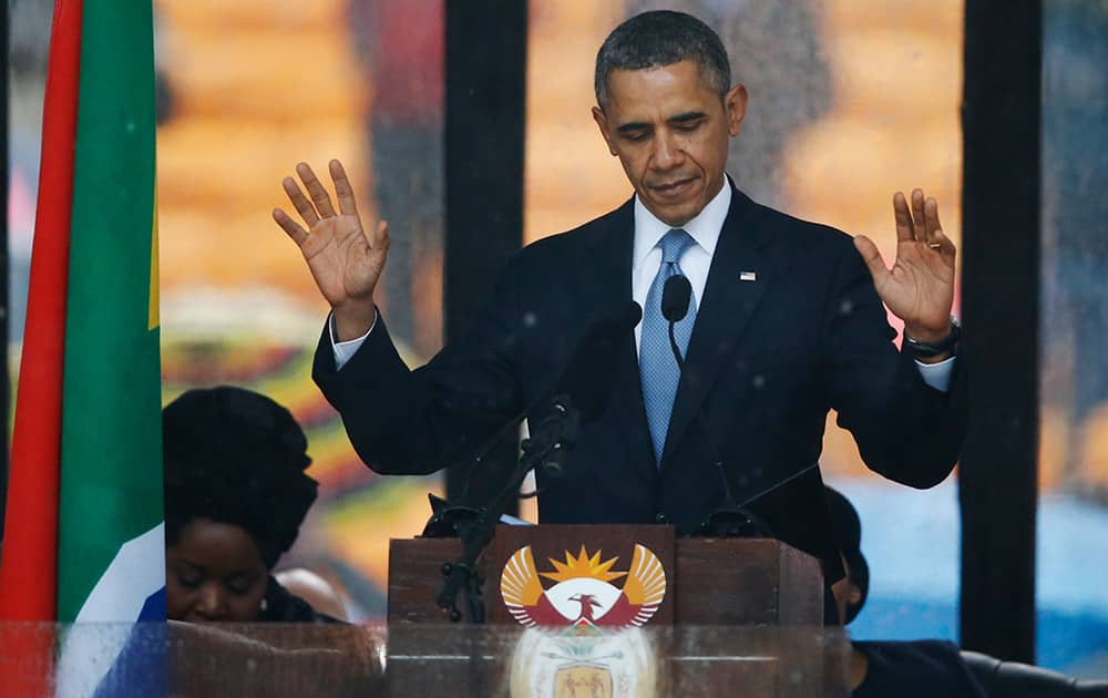 President Barack Obama acknowledges applause before speaking at the memorial service for former South African president Nelson Mandela at the FNB Stadium in Soweto near Johannesburg.