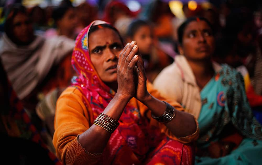 A Dalit woman, member of the outcast community once known as untouchables, listens to a speaker with folded hands at a sit in protest on Human Rights Day near the Indian Parliament in New Delhi.