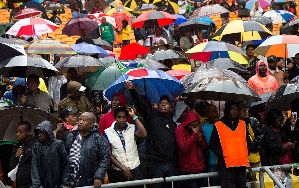 People watch as President Barack Obama speaks to crowds attending the memorial service for former South African president Nelson Mandela at the FNB Stadium in Soweto near Johannesburg.