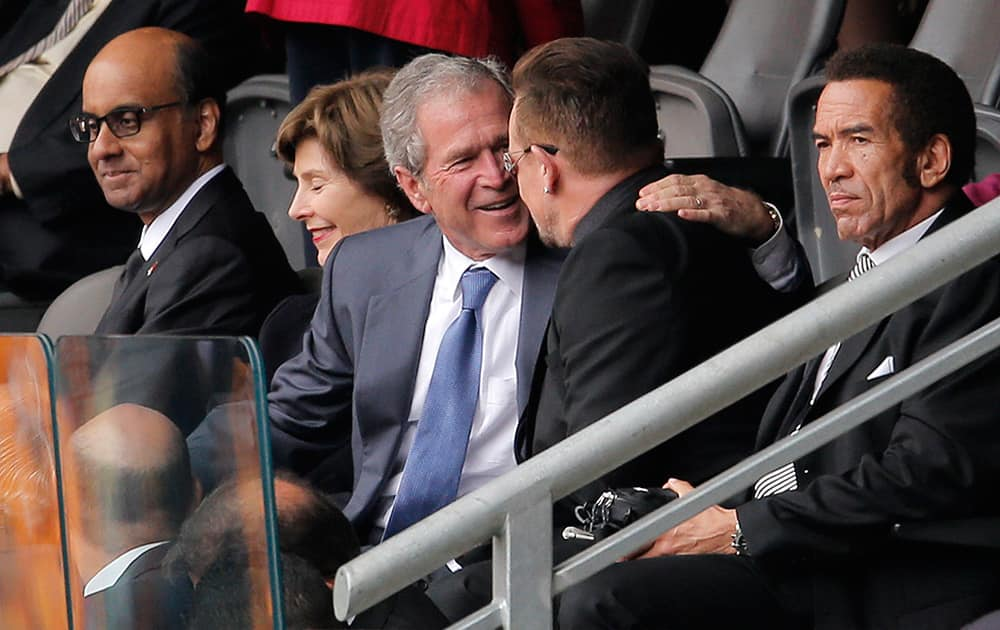 Former US President George W. Bush embraces Irish rock star Bono during the memorial service for former South African president Nelson Mandela at the FNB Stadium in Soweto, near Johannesburg, South Africa.