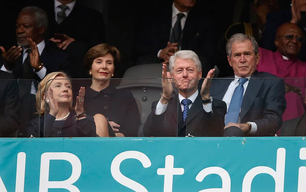 From left, Former US Secretary of State Hillary Rodham Clinton, Laura Bush, Former US President Bill Clinton and Former US President George W. Bush listen to speakers during the memorial service for former South African president Nelson Mandela at the FNB Stadium in Soweto near Johannesburg.