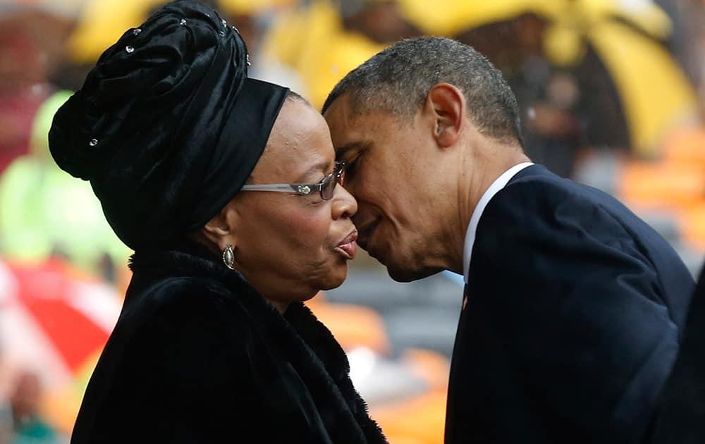 President Barrack Obama kisses Nelson Mandela`s widow Graca Machel during the memorial service for former South African president Nelson Mandela at the FNB Stadium in Soweto near Johannesburg.