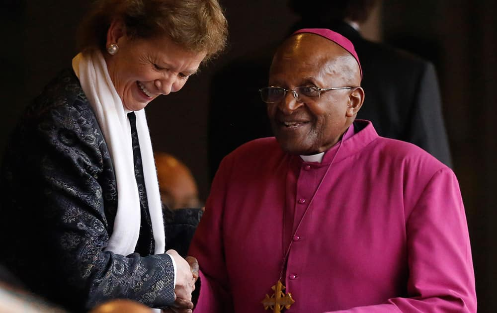 Former Bishop Desmond Tutu, right, and Irish President Mary Robinson arrive for the memorial service for former South African president Nelson Mandela at the FNB Stadium in Soweto near Johannesburg.
