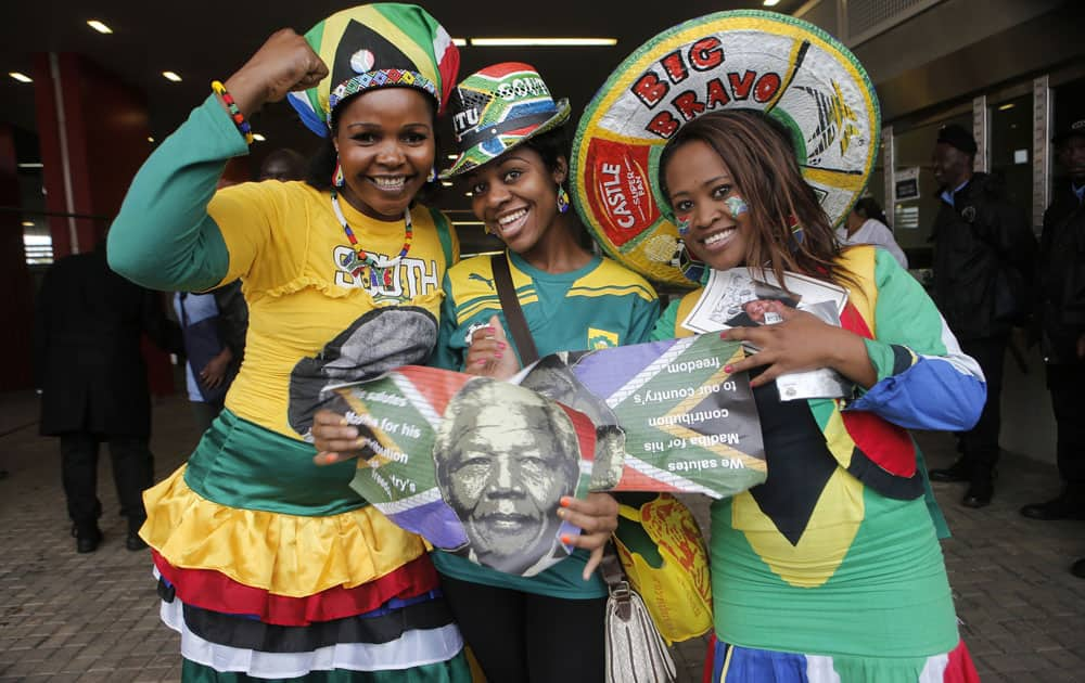 Women pose for a photo as they arrive for the memorial service for former South African president Nelson Mandela at the FNB Stadium in Soweto, near Johannesburg, South Africa.