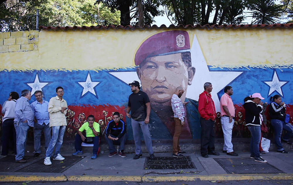 Residents wait in line to enter a polling station to vote in front of a wall painting depicting late president Hugo Chavez during municipal elections in Caracas, Venezuela.
