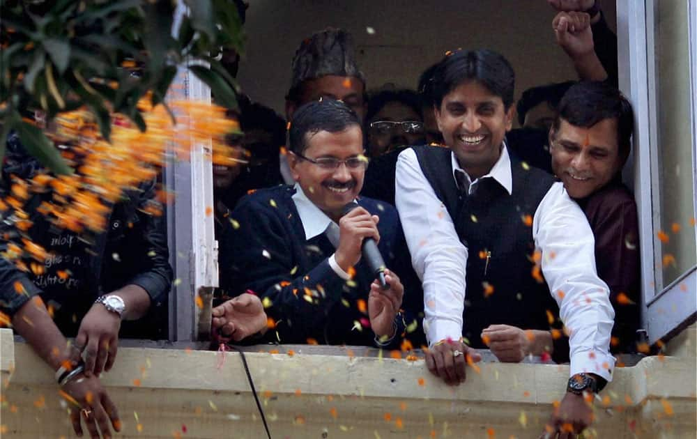 Aam Aadmi Party convener Arvind Kejriwal addresses supporters who were celebrating after the party`s excellent show in Delhi Assembly elections, in New Delhi.