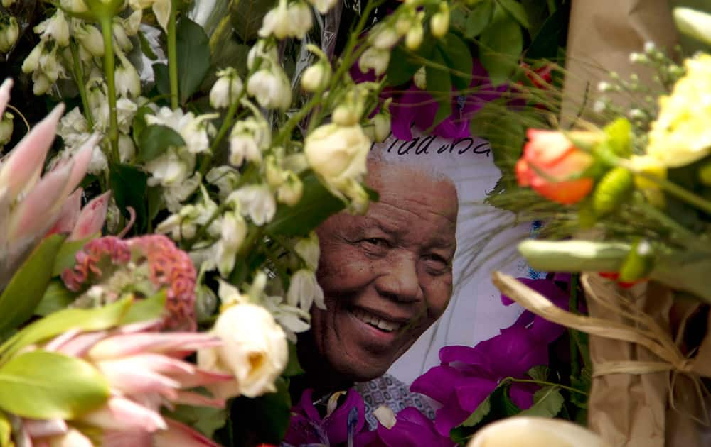 A picture of South Africa`s former president Nelson Mandela is seen placed in a pile of flowers outside his home in Johannesburg, South Africa.