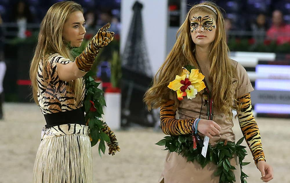 Swiss show jumping rider Jane Richard Phillips, left, and American Jennifer Gates daughter of Bill Gates, right, walk through the course during the equestrian