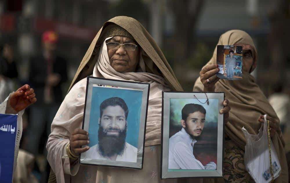 Pakistani Delshad Fazil, 60, holds photographs of her missing son, left, and nephew, during a protest near the parliament in Islamabad, Pakistan.