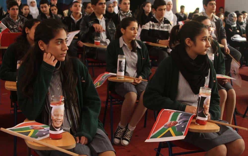 Lebanese students with South Africa flags and candles with the portraits of late South African leader Nelson Mandela on their desks listen to a lecture on his life at their school, in the southern port city of Sidon, Lebanon.