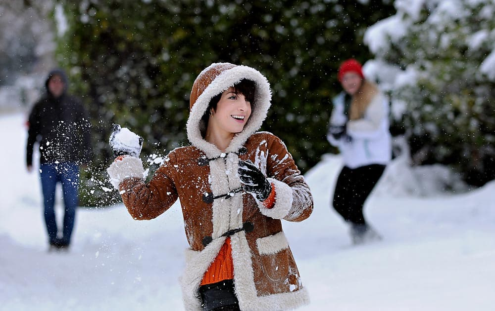 Oregon State University senior Suzy Slack takes aim during a snowball fight with friends in downtown Corvallis, Ore.