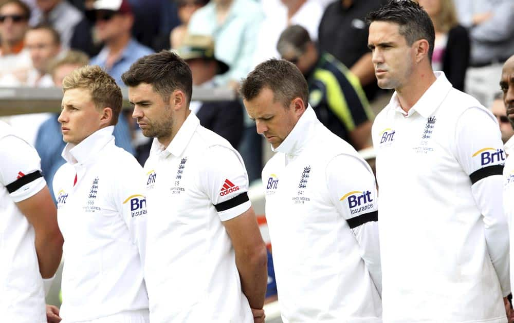England cricket players from right, Kevin Pietersen, Graeme Swann, James Anderson and Joe Root take a moment of silence for former South African President Nelson Mandela before the start of the second Ashes cricket test match against Australia in Adelaide.