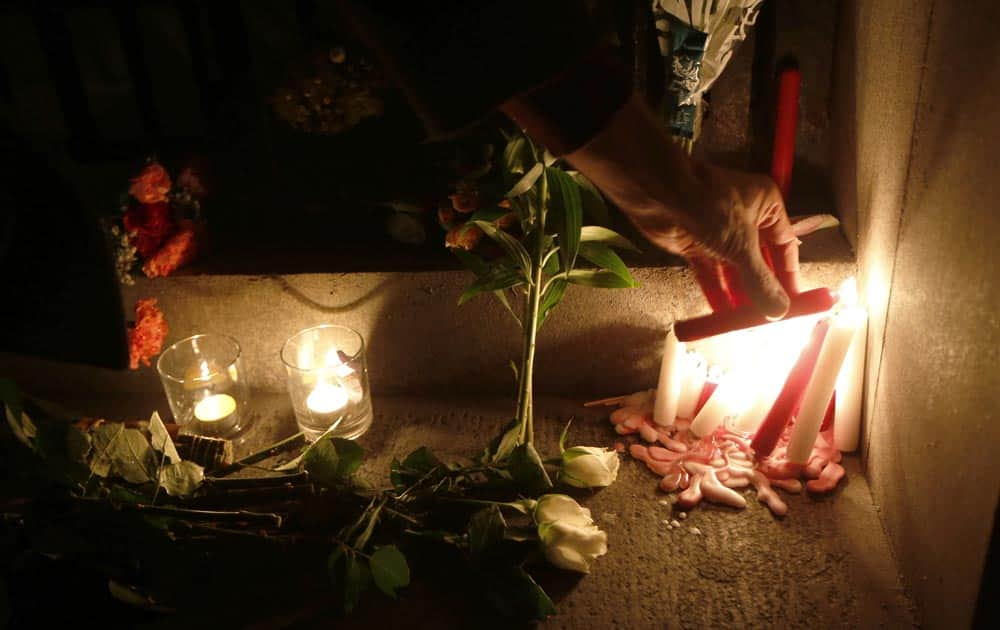 A man lights a candle for Nelson Mandela outside South AfricaN High Commission in London.