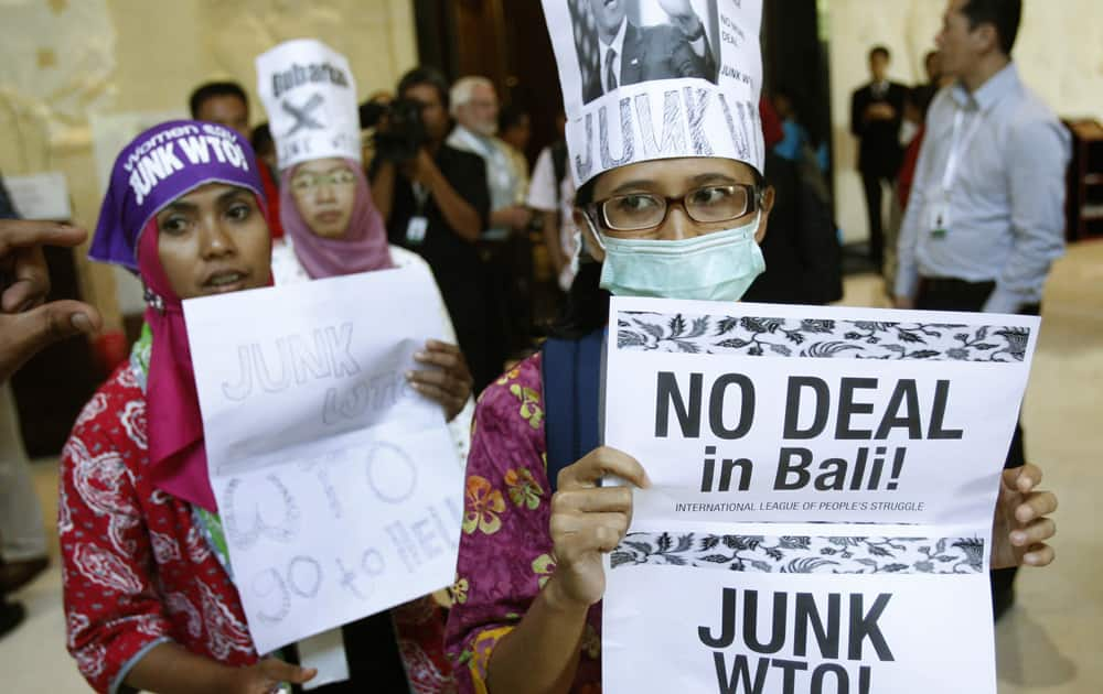 Activist holds a banner during a protest against the World Trade Organization (WTO) in Bali, Indonesia. Indonesia is hosting the World Trade Organization Ministerial Conference from Dec. 3- 6.