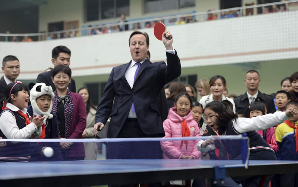 British Prime Minister David Cameron plays table tennis during his visit to a primary school in Chengdu in southwest China`s Sichuan province.