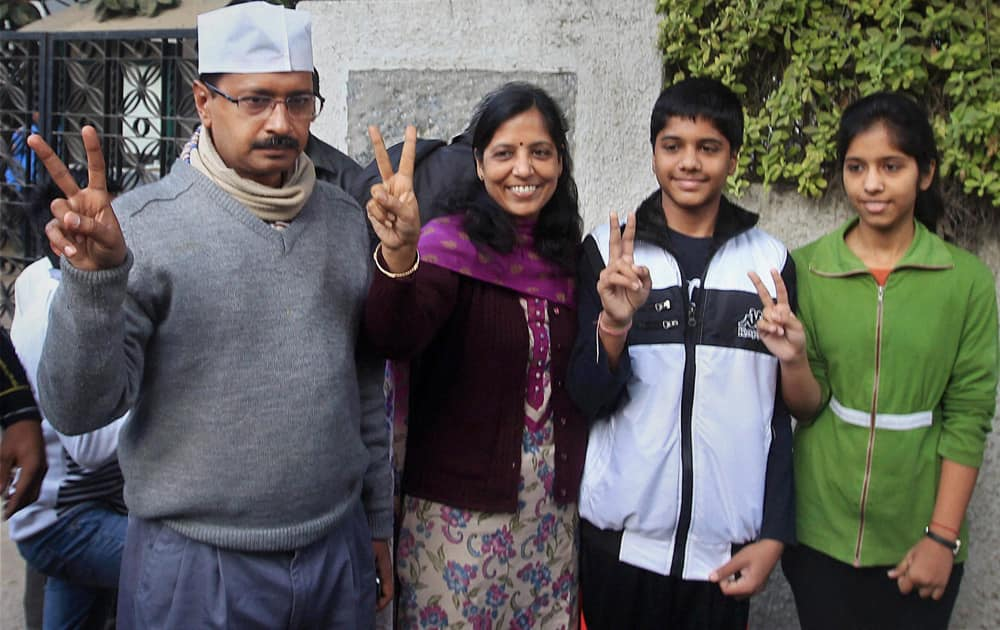 AAP convener Arvind Kejriwal flashes victory sign with his family after casting vote for Delhi Assembly elections, at a polling booth in New Delhi.