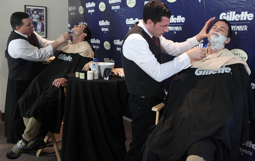 New England Patriots fan Tim Sullivan, right, and Patriots wide receiver Danny Amendola, left, say goodbye to their Mo`s with help from barbers from The Art of Shaving at Gillette Stadium in Foxborough, Mass.