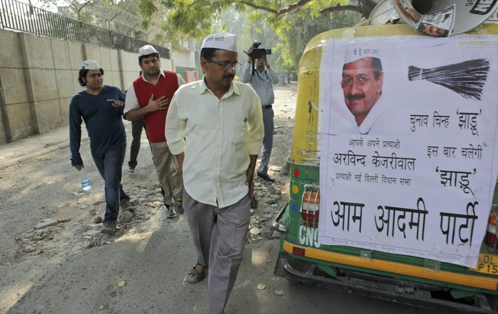 Arvind Kejriwal looks at an auto rickshaw displaying a poster in support of his party, ahead of the Delhi state assembly elections in New Delhi.