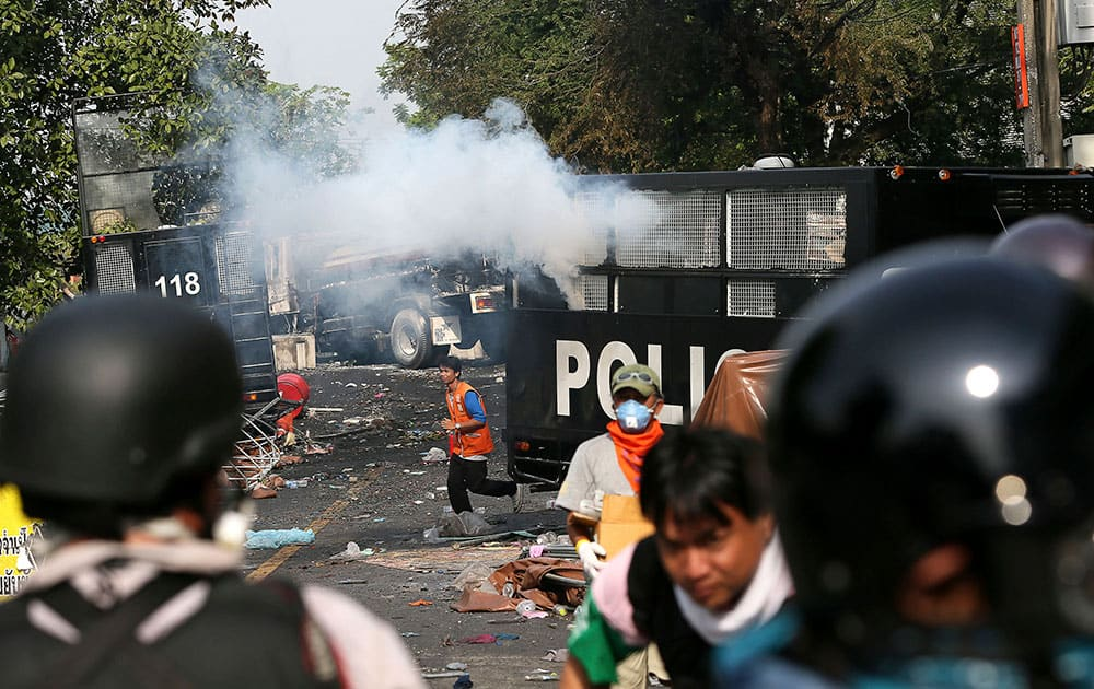 Anti-government protesters run for cover after police fires a tear gas shell to disperse them during a protest rally outside government offices which are barricaded by police forces, in Bangkok, Thailand.