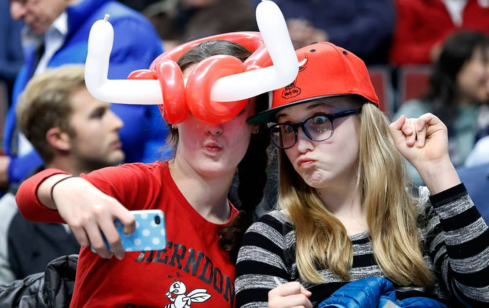 Saunders Ervin, left, and Samantha Walter, of Chicago, make a cellular phone portrait of themselves during the first half of an NBA basketball game between the Chicago Bulls and the New Orleans Pelicans, in Chicago.