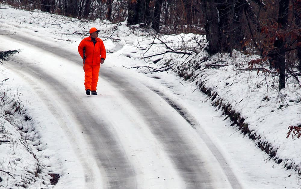 A hunter looks into the woods as he walks down a snow covered road in West Liberty, Pa.
