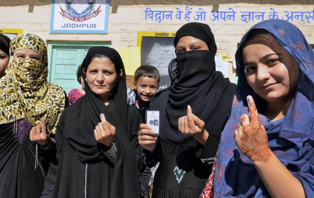 Muslim women show their ink-marked fingers after casting their votes for state assembly elections in Jodhpur.