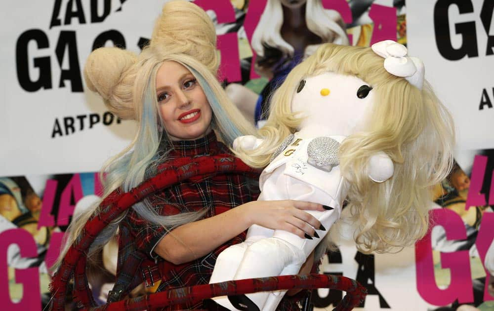 Lady Gaga poses for photographers with a Hello Kitty doll during a press conference to promote her album
