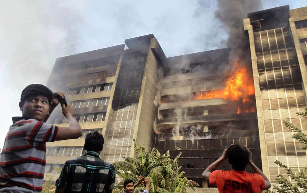 People take pictures during a fire at a nine-story garment factory in Gazipur, near Dhaka, Bangladesh.