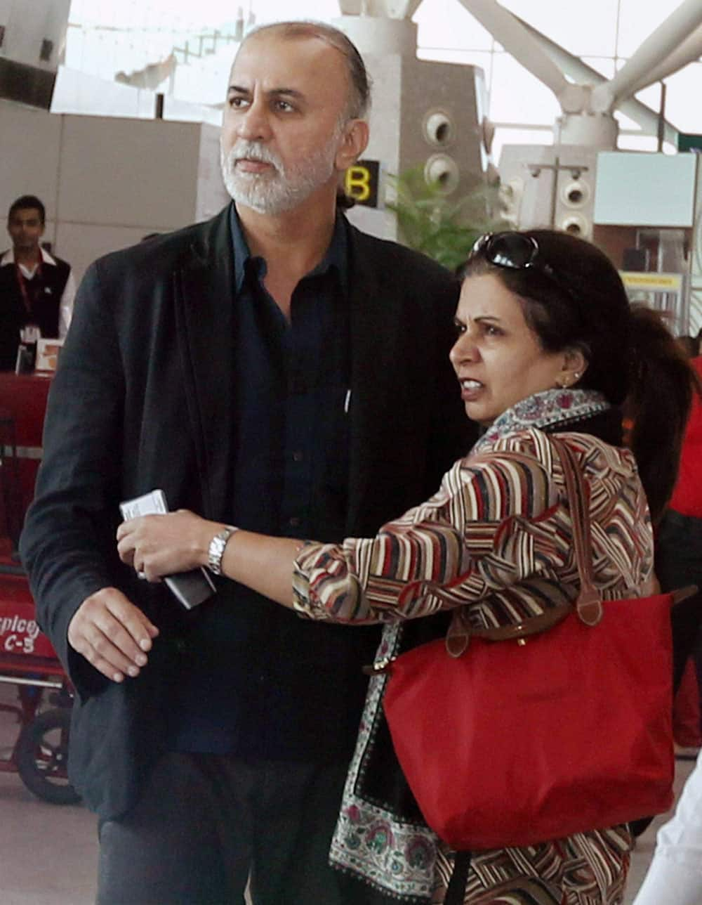 Tehelka editor-in-chief Tarun Tejpal with his wife at the Indira Gandhi International Airport in New Delhi on Friday before boarding flight to Goa. Tejpal is accused of sexually assaulting a woman journalist.