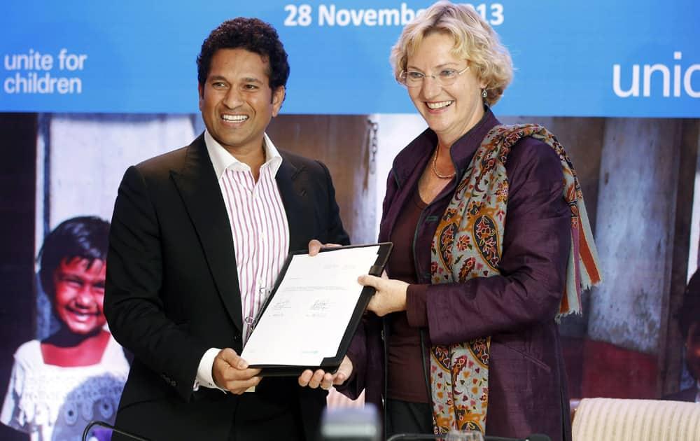 Sachin Tendulkar and UNICEF Regional Director for South Asia Karin Hulshof display a certificate declaring Tendulkar UNICEF ambassador for South Asia, in Mumbai.