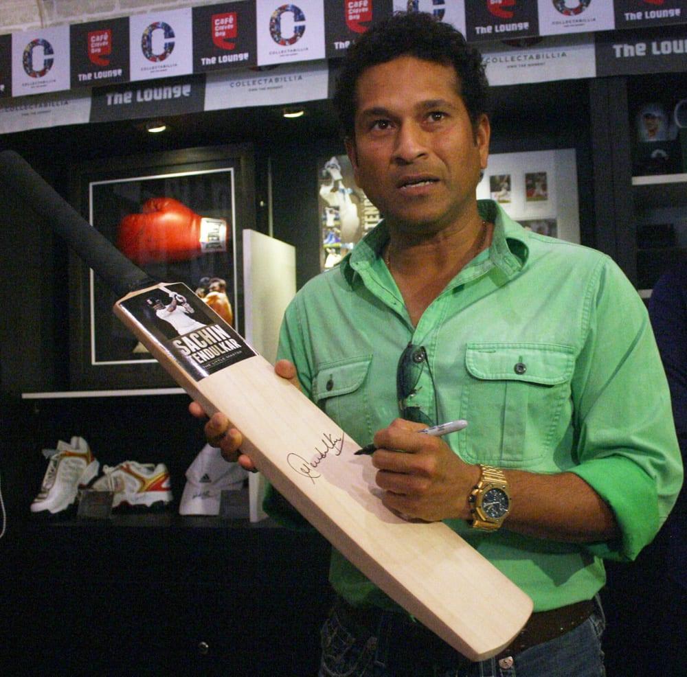 Sachin Tendulkar signing a bat during a launch event in Mumbai.
