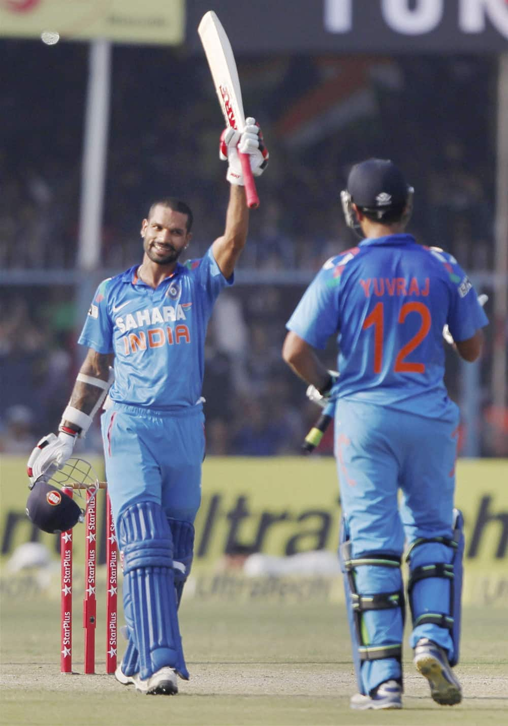 Shikar Dhawan raises the bat after his century during the last ODI cricket match against West Indies at Green Park Stadium in Kanpur.
